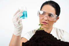 La mujer del científico analiza el líquido azul fotos de archivo libres de regalías