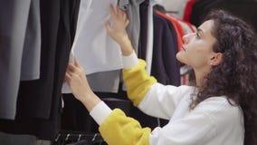 La mujer del cliente está examinando precios en las camisetas juguetonas en tienda de la ropa almacen de metraje de vídeo
