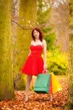La mujer del comprador del otoño con venta empaqueta al aire libre en parque Fotos de archivo libres de regalías
