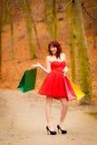 La mujer del comprador del otoño con venta empaqueta al aire libre en parque Imagenes de archivo