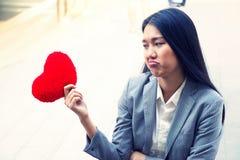 La mujer del corazón quebrado está llevando a cabo el corazón rojo con la expresión facial triste Fotos de archivo