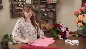 La mujer del decorador está cortando el papel de embalaje para los ramos florales en una tienda almacen de video