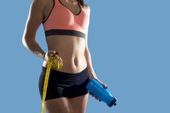 La mujer del deporte que sostiene la botella de agua y la medida graban mostrar el ABS y el estómago perfectos delgados Imagenes de archivo