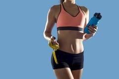 La mujer del deporte que sostiene la botella de agua y la medida graban mostrar el ABS y el estómago perfectos delgados Imagen de archivo