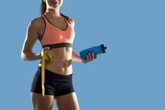 La mujer del deporte que sostiene la botella de agua y la medida graban mostrar el ABS y el estómago perfectos delgados Fotografía de archivo libre de regalías