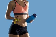 La mujer del deporte que sostiene la botella de agua y la medida graban mostrar el ABS y el estómago perfectos delgados Foto de archivo libre de regalías