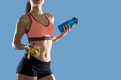 La mujer del deporte que sostiene la botella de agua y la medida graban mostrar el ABS y el estómago perfectos delgados Imagen de archivo libre de regalías