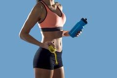 La mujer del deporte que sostiene la botella de agua y la medida graban mostrar el ABS y el estómago perfectos delgados Fotos de archivo libres de regalías