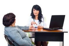 La mujer del doctor da píldoras al paciente en oficina Fotografía de archivo libre de regalías