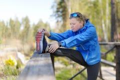 La mujer del ejercicio que estira la pierna del tendón de la corva muscles el ru al aire libre duing Imágenes de archivo libres de regalías