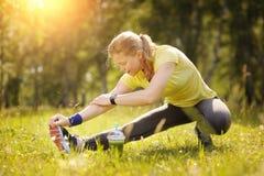 La mujer del ejercicio que estira la pierna del tendón de la corva muscles el ru al aire libre duing Imagenes de archivo
