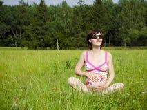 La mujer del embarazo se está sentando en una hierba Fotografía de archivo libre de regalías