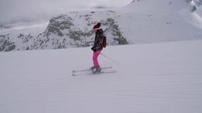 La mujer del esquiador del principiante está esquiando abajo de la cuesta debajo de los levantadores almacen de metraje de vídeo