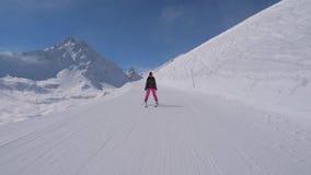 La mujer del esquiador del principiante está esquiando abajo de las montañas Nevado del fondo de la cuesta almacen de video