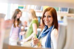 La mujer del estudiante de la biblioteca de la High School secundaria elige el libro Imágenes de archivo libres de regalías