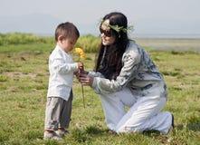 La mujer del Hippie da a hijo una flor amarilla Foto de archivo