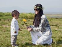 La mujer del Hippie da a hijo una flor amarilla Imagen de archivo