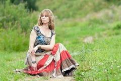 La mujer del hippie se sienta en una hierba Fotos de archivo libres de regalías