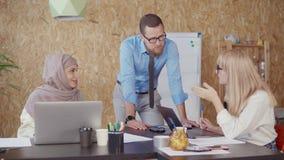 La mujer del hombre, rubia y musulmán está discutiendo en área de la oficina en día laborable metrajes