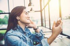 La mujer del inconformista disfruta de música que escucha del teléfono app Foto de archivo libre de regalías