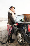 La mujer del inconformista llena el coche de la gasolina Imagen de archivo libre de regalías