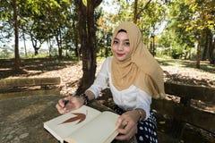 La mujer del Islam escribe el diario fotografía de archivo