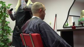 La mujer del peluquero cortó al cliente masculino en peluquero del salón de belleza 4K almacen de metraje de vídeo