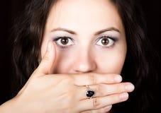 La mujer del primer mira derecho en la cámara en un fondo negro Ella cubrió su boca con su mano expresa Fotografía de archivo libre de regalías