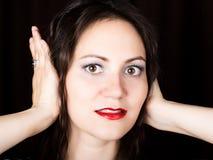La mujer del primer mira derecho en la cámara en un fondo negro la mujer de risa cubre sus oídos con sus manos Foto de archivo libre de regalías