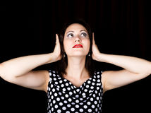 La mujer del primer mira derecho en la cámara en un fondo negro la mujer de risa cubre sus oídos con sus manos Fotos de archivo