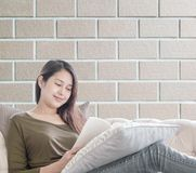 La mujer del primer que se sienta en el sofá para leer un libro en tiempo libre por la tarde en fondo texturizado pared de ladril Fotografía de archivo libre de regalías