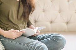 La mujer del primer que se sienta en el sofá para leer un libro en tiempo libre por la tarde, relaja época del concepto asiático  Imagenes de archivo