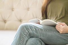 La mujer del primer que se sienta en el sofá para leer un libro en tiempo libre por la tarde, relaja época del concepto asiático  Fotos de archivo libres de regalías