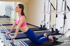 La mujer del reformador de Pilates abajo estira ejercicio Imagen de archivo
