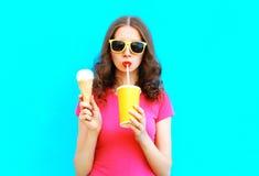 La mujer del retrato de la moda bebe el zumo de fruta del helado de la taza y de los controles sobre azul colorido Fotografía de archivo libre de regalías