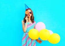 La mujer del retrato en un casquillo del cumpleaños sostiene un aire que son los globos coloridos están soplando los labios se ci Fotografía de archivo