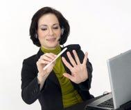 La mujer del servicio de atención al cliente hace sus clavos en el reloj Foto de archivo libre de regalías
