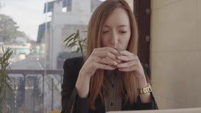 La mujer del trabajador del Freelancer se está sentando en café con el ordenador portátil y el trabajo, sorbiendo té almacen de video