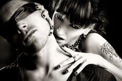 La mujer del vampiro muerde a un hombre oculto Fotografía de archivo