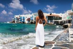 La mujer del viajero en el vestido blanco disfruta de la visión a la ciudad de la isla de Mykonos fotografía de archivo libre de regalías