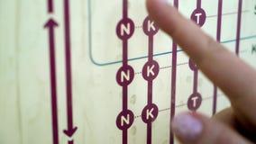 La mujer del viajero encuentra la mejor ruta en mapa en la estación de metro metrajes