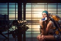 La mujer del viajero está esperando un vuelo Imagen de archivo libre de regalías