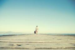 La mujer del viajero está caminando al destino con su maleta Foto de archivo libre de regalías