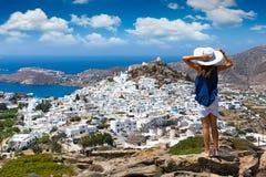 La mujer del viajero pasa por alto la ciudad del IOS de la isla en las Cícladas en Grecia fotos de archivo libres de regalías