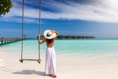 La mujer del viajero se coloca cerca a un oscilación en una playa tropical Fotos de archivo libres de regalías