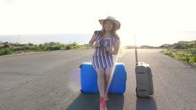 La mujer del viajero se sienta en la maleta y mira lejos en el camino metrajes