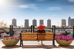 La mujer del viajero se sienta en un banco en la perla en Doha, Qatar foto de archivo libre de regalías