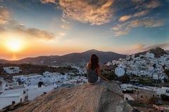 La mujer del viajero se sienta en una roca en la isla de IOS, Cícladas, Grecia fotos de archivo libres de regalías