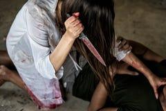 La mujer del zombi o el fantasma de la mujer que sostiene el cuchillo matará a gente del hombre fotografía de archivo libre de regalías