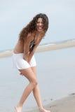 La mujer delgada con el cuerpo hermoso que lleva la mini falda y el sujetador presentan en la playa Imagen de archivo